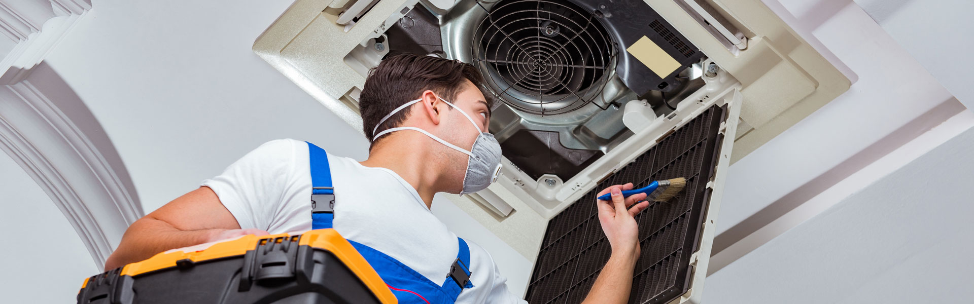 Worker Servicing Ceiling AC